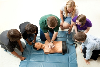 Group learning CPR (cardiopulmonary resuscitation) in school.